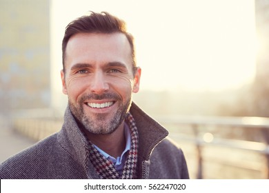 Portrait of happy man smiling outdoors during cold winter day