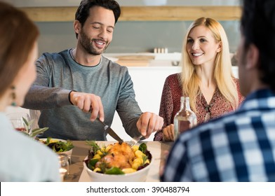 Portrait of a happy man taking his share of food. Happy family reunion at house. Young friend meeting for lunch at home. Friends having dinner or lunch at home.