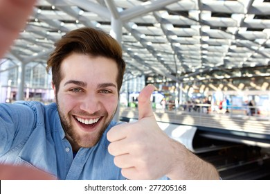 Portrait of a happy man taking selfie with thumbs up