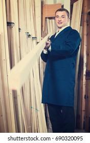 portrait of happy man in uniform choosing compressed densified wood in picture framing atelier