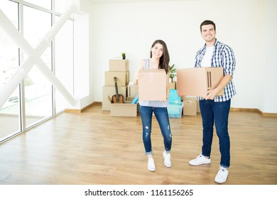 Portrait of happy man and woman carrying moving cardboard boxes in new luxury home