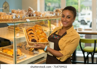 Portrait of a happy mature African woman holding basket with pastry at her bakery smiling joyfully to the camera copyspace offering dessert food eating cafe coffee shop delicious freshly baked service