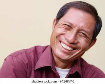 Portrait of happy mature Asian man smiling and looking at camera. Copy space