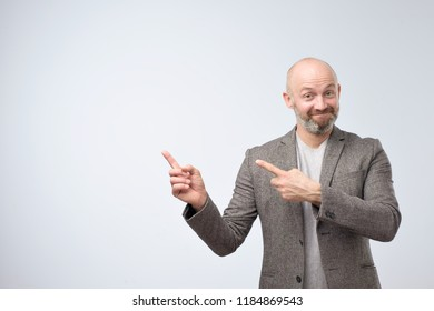 Portrait of a happy mature businessman in casual suit pointing finger away over white background trying to pay your attention to important information. Place for text