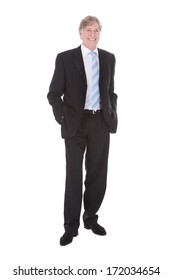 Portrait Of Happy Mature Businessman With Hand In Pocket Over White Background