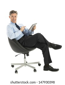 Portrait of happy mature businessman pointing at digital tablet while sitting on office chair against white background