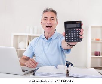 Portrait Of Happy Mature Businessman Showing Profit