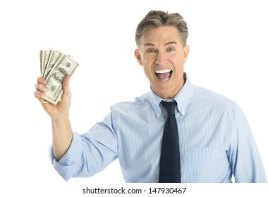 Portrait of happy mature businessman showing dollar bills against white background