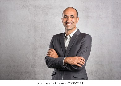 Portrait of happy mature businessman smiling on grey background. Successful senior leader in formal standing against grey wall with crossed arms. Satisfied man feeling proud and looking at camera.