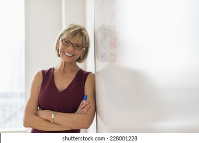 Portrait of happy mature businesswoman leaning on whiteboard in office