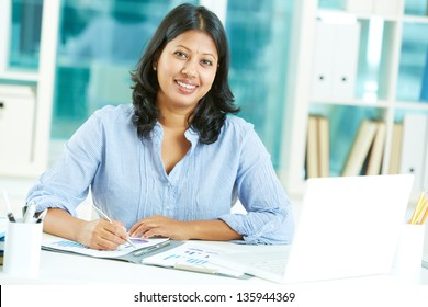 Portrait of happy mature businesswoman looking at camera while working in office