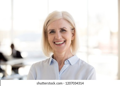 Portrait of happy mature businesswoman posing in modern light office, headshot of smiling middle-aged female employee look in camera making professional business picture, woman photoshoot in boardroom