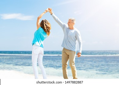 Portrait Of Happy Mature Couple Dancing On The Beach