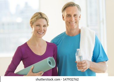 Portrait of happy mature couple with exercise mat, water bottle and towel in health club