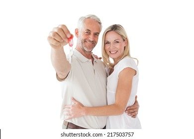 Portrait of happy mature couple holding new house key over white background