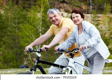 Portrait of happy mature couple on bicycles