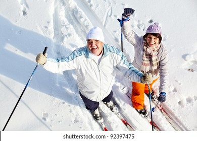 Portrait of happy mature couple of skiers laughing