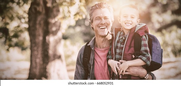 Portrait of happy mature father and elementary son in forest