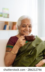 Portrait of happy mature Indian woman having tea