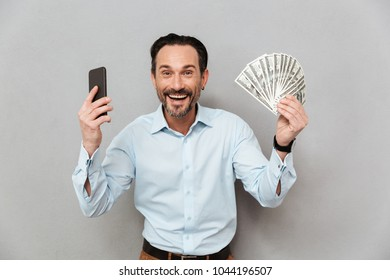 Portrait of a happy mature man dressed in shirt holding mobile phone while standing and showing money banknotes over gray background