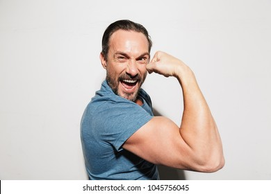 Portrait of a happy mature man dressed in t-shirt showing biceps isolated over white background