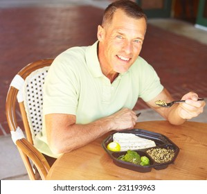 Portrait of happy mature man eating baked tilapia served with broccoli and wild rice at restaurant