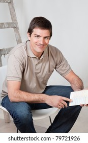 Portrait of happy mature man holding color swatch in his hand