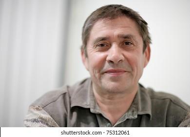 Portrait of happy mature man looking at camera. Closeup, shallow DOF.