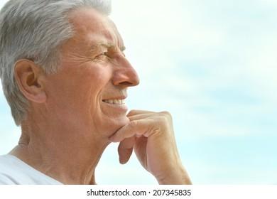 Portrait of happy mature man over blue sky
