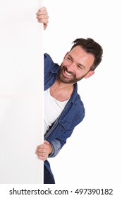 Portrait of happy mature man peeking over blank poster sign on white background