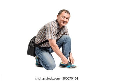 Portrait of a happy mature man in scott shirt and blue jeans tying his shoes. Isolated full length on white background with copy space