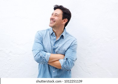 Portrait of happy mature man standing with arms crossed against white wall and looking away