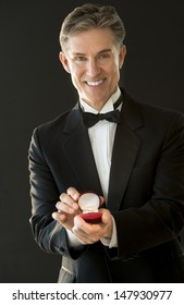 Portrait of happy mature man in tuxedo holding ring box isolated on black background