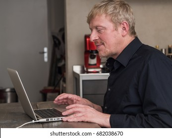 Portrait of a happy, mature man working on laptop at home