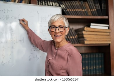 Portrait of happy mature professor teaching mathematics to students in a library. Senior smiling woman solving math problem while writing on white board. Portrait of tutor looking at camera.