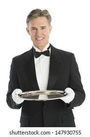 Portrait of happy mature waiter in tuxedo holding serving tray against white background