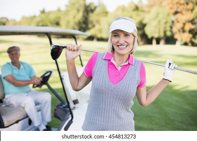 Portrait of happy mature woman carrying golf club while standing by man