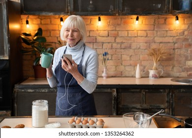 Portrait of happy mature woman chilling in kitchen while cooking. Smiling senior woman with cup of tea listening music on mobile phone in kitchen