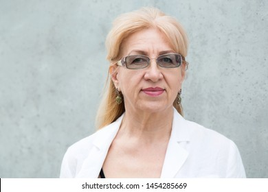 Portrait of happy mature woman in glasses, age 60 years against the gray wall.