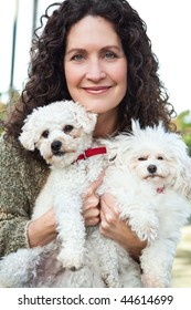 A portrait of a happy mature woman with her dogs outdoor
