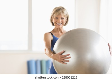 Portrait of happy mature woman holding yoga ball at home