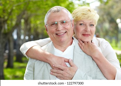 Portrait of happy mature woman hugging her husband outside