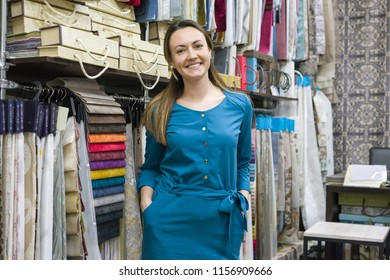 Portrait of happy mature woman owner in interior fabrics store, background fabric samples. Small business home textile shop