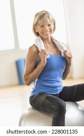 Portrait of happy mature woman with towel around neck sitting on fitness ball at home
