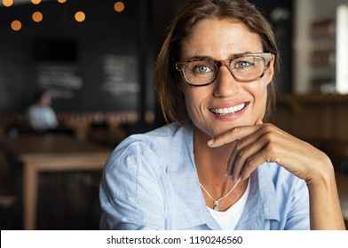 Portrait of happy mature woman wearing eyeglasses and looking at camera. Closeup face of smiling woman sitting in cafeteria with hand on chin. Successful lady in a cafe pub.
