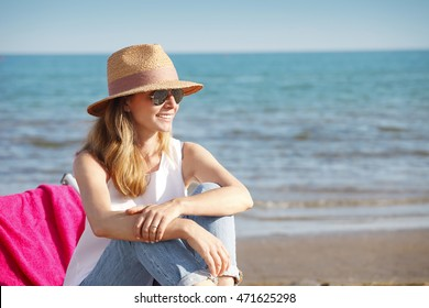 Portrait of happy mature woman wearing straw hat and sunglasses while at the beach on a sunny day.