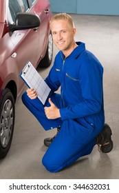 Portrait Of A Happy Mechanic Holding Clipboard