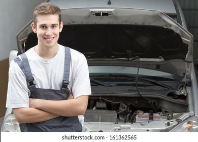 Portrait of happy mechanic repairing under car hood