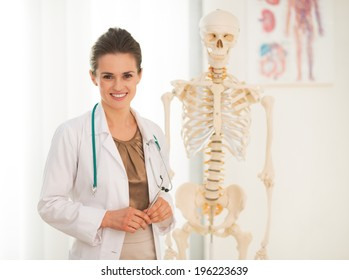 Portrait of happy medical doctor woman teaching anatomy using human skeleton model
