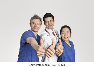 Portrait of a happy medical team gesturing thumbs up over gray background